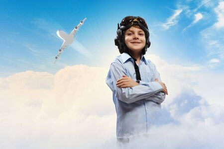 inair: Image of little boy in pilots helmet with flying airplane in background