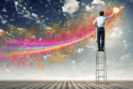 young man standing with back on ladder painting splashes photo