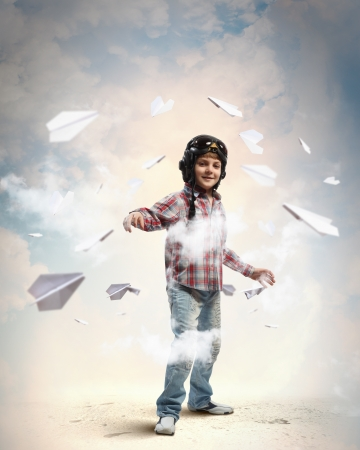 airman: Image of little boy in pilots helmet with paper airplanes in background