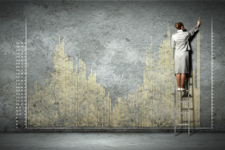 businesswoman standing on ladder drawing diagrams and graphs on wall Stock Photo - 17532345