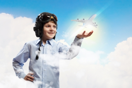 looking around: Image of little boy in pilots helmet with toy airplane in hand