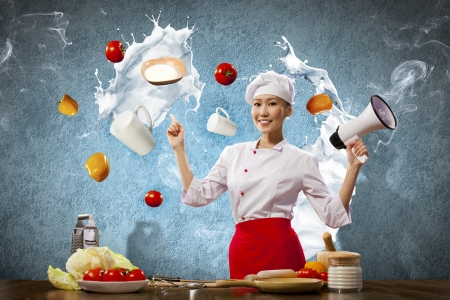 female chef: Asian female cook holding megaphone vegetables flying in air