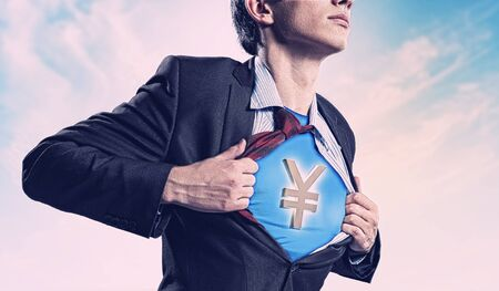 Image of young businessman in superhero suit with yen sign on chest Stock Photo - 17533510