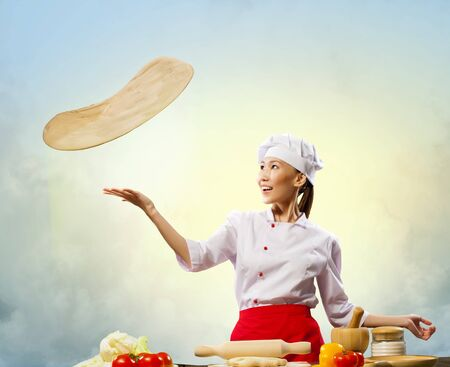 Asian female cook making pizza standing against color background photo