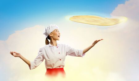 inair: Asian female cook making pizza standing against color background Stock Photo