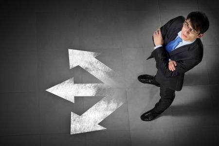 business decisions: Top view of businessman standing against directions background