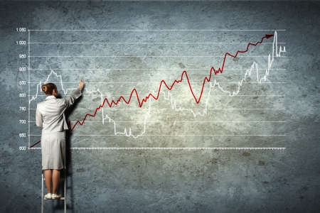 graphs: businesswoman standing on ladder drawing diagrams and graphs on wall