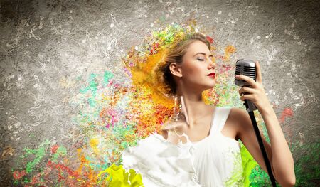 Image of female blonde singer holding microphone against color background with closed eyes Stock Photo - 17579109