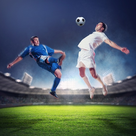 two football players in jump to strike the ball at the stadium photo