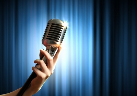 micro recording: Single retro microphone against blue curtains closed on the background Stock Photo