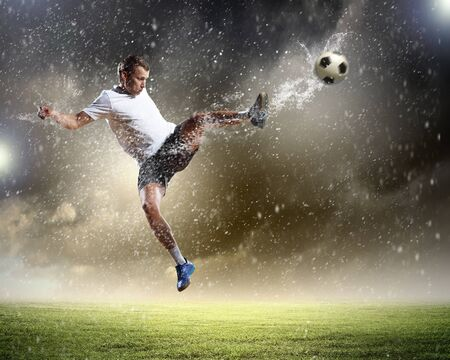 downpour: football player in white shirt striking the at the stadium under the rain Stock Photo