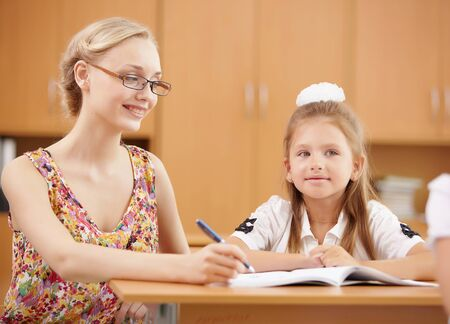 Young female teacher working with children at school Stock Photo - 17578989