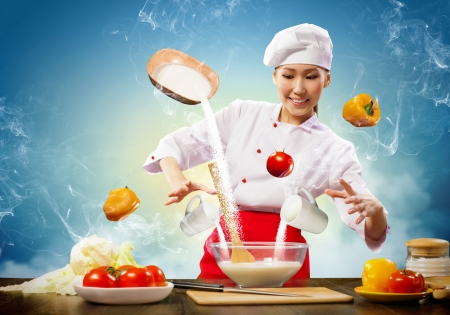 Asian female cooking with magic against color background Stock Photo - 17578926