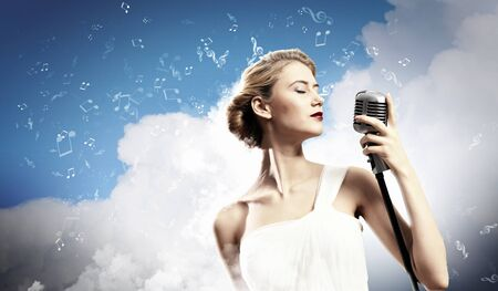 Image of female blonde singer holding microphone against clouds background with closed eyes Stock Photo - 17578834