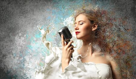 Image of female blonde singer holding microphone against color background with closed eyes Stock Photo - 17579122