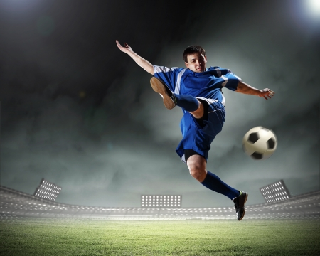 football player in blue shirt striking the ball aloft at the stadium