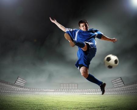 Joueur de football en chemise bleue frapper la balle en l'air dans le stade Banque d'images - 17578984