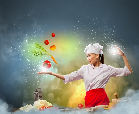 Asian female cooking with magic against color background Stock Photo - 17578844