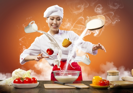 Asian female cooking with magic against color background Stock Photo - 17578920