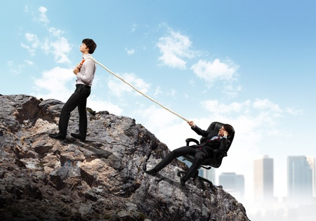atop: Image of two young businessmen pulling rope atop of mountain against city background