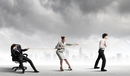 pulling rope: Image of three businesspeople pulling rope against city background