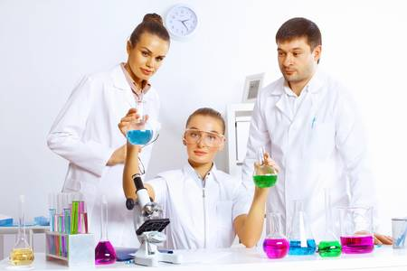 Young female scientist working with liquids in laboratory Stock Photo - 17578780