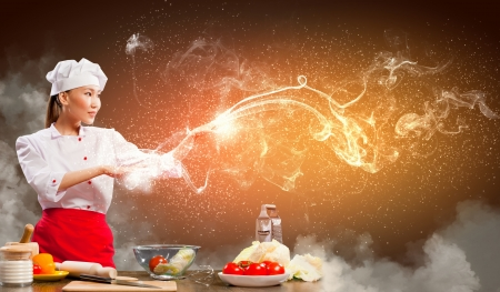 Asian female cooking with magic against color background Stock Photo - 17578924