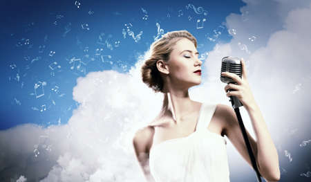 Image of female blonde singer holding microphone against clouds background with closed eyes Stock Photo - 17578845