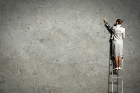 businesswoman standing on ladder drawing diagrams and graphs on wall Stock Photo - 17579069