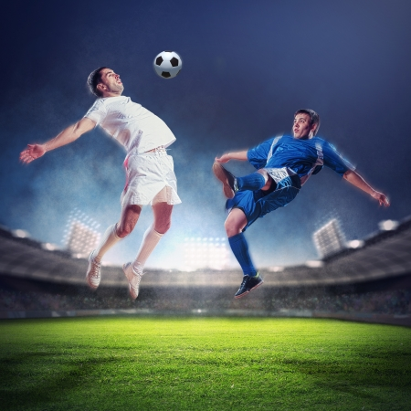 football stadium: two football players in jump to strike the ball at the stadium
