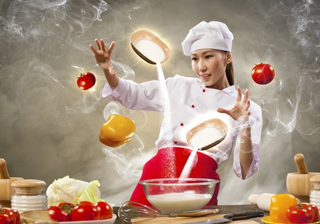 Asian female cooking with magic against color background Stock Photo - 17578980