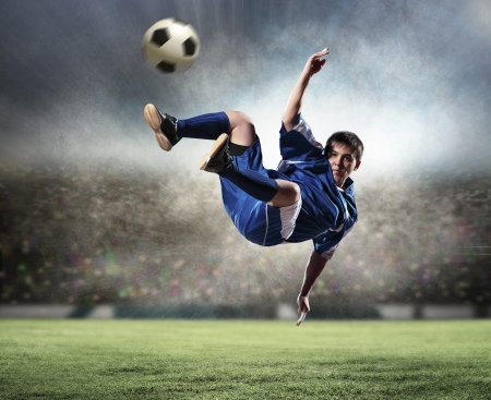downpour: football player in blue shirt striking the ball aloft at the stadium