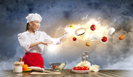 Asian female cooking with magic against color background Stock Photo - 17579116