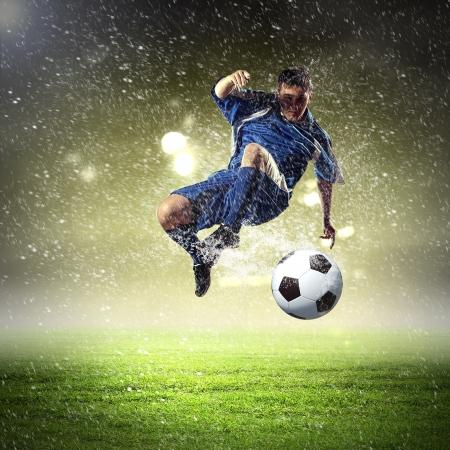 jugadores de futbol: jugador de fútbol en la camisa azul de golpear la pelota en el aire, en el estadio bajo la lluvia