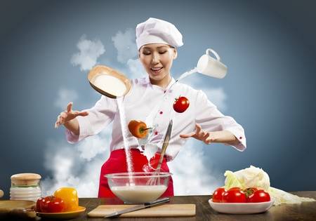 Asian female cooking with magic against color background Stock Photo - 17578763