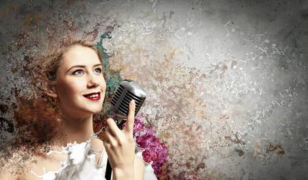 Image of female blondу singer holding microphone against color background Stock Photo - 17579074