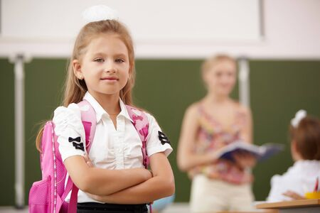 Little blonde girl studying at school class photo