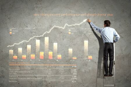 businessman standing on ladder drawing diagrams and graphs Stock Photo - 17621222