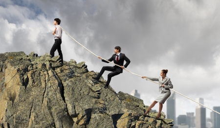Image of three businesspeople pulling rope against city background photo