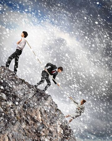 atop: Image of three businesspeople pulling rope atop of mountain under falling snow Stock Photo