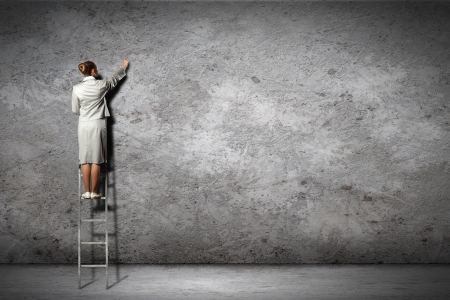 businesswoman standing on ladder drawing diagrams and graphs on wall Stock Photo - 17614277