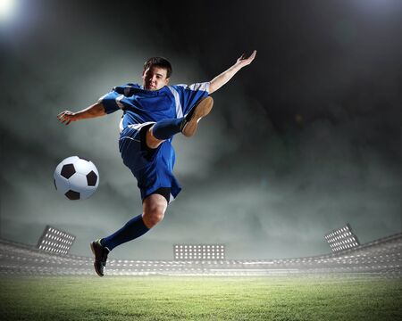 football player in blue shirt striking the ball aloft at the stadium photo