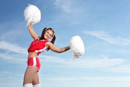 Young beautiful female cheerleader in uniform jumping high Stock Photo - 17614171