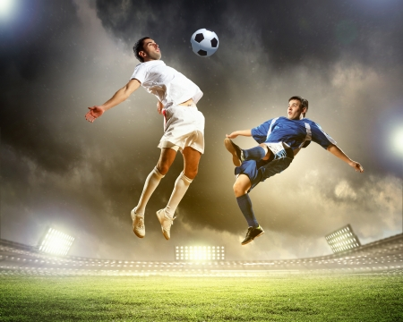stadium: two football players in jump to strike the ball at the stadium