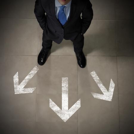 Bovenaanzicht van zakenman staande tegen richtingen achtergrond