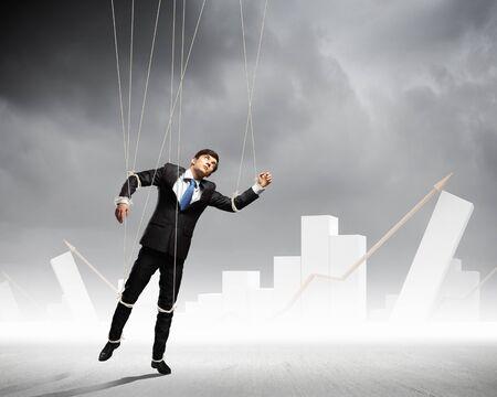 obedecer: Imagen de hombre de negocios que cuelgan en cadenas como la fotografía conceptual marioneta