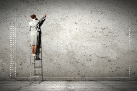 businesswoman standing on ladder drawing diagrams and graphs on wall Stock Photo - 17619544