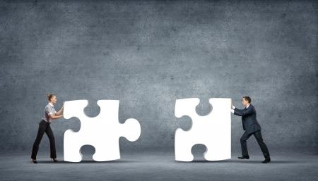 piezas de rompecabezas: Equipo de gente de negocios colaboren levantando piezas de puzzle como una soluci�n a un problema Foto de archivo