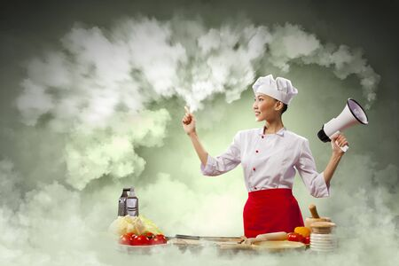 inair: Asian female young cook smiling holding megaphone Stock Photo