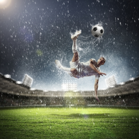football player in white shirt striking the ball at the stadium under the rain Stock Photo - 17672369